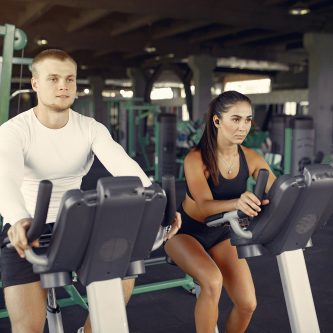 Confidentgym_Sports couple in a sportswear training in a gym Begeleiding bij het behalen van jouw doelstellingen