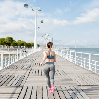 Confidentgym Attractive Sporty Woman Running on Bridge